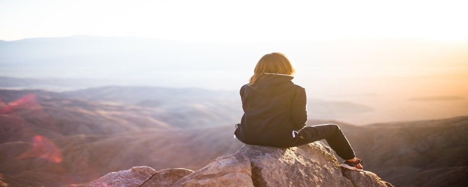 Woman watching a sunset on a cliff